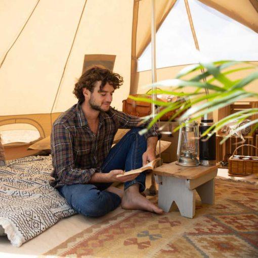 Một người đàn ông đang ngồi đọc sách trong Lều mông cổ Naturehike Glamping Pyramid 12.3